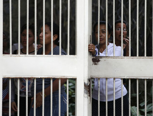 Women shelter themselves during clashes in Caracas