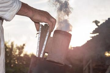 Beekeeper makes smoke under hive. Beekeeping. Apiary. Man's hand holds smoke