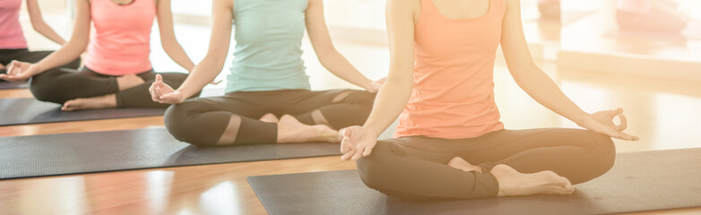 Fotobehang School de yoga woman group exercising and sitting in yoga lotus position in yoga classes