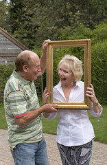 Elderly couple playing with a picture frame in a garden setting