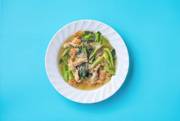 Top view of famous fried noodles with pork, chinese kale and broccoli. Isolated on blue background and clipping path