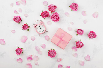 Gift box, alarm clock, petals and pink rose flowers on white table top view in flat lay style. Greeting for Mother or Woman day concept.