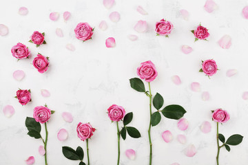 Beautiful pink rose flowers on white table top view. Wedding mockup in flat lay style.