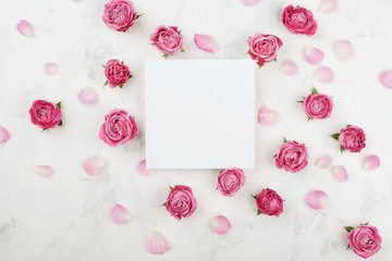 Wedding mockup with white paper list, pink rose flowers and petals on light table top view. Beautiful floral pattern. Flat lay style.