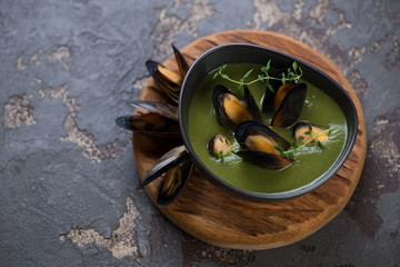 Spinach cream-soup with mussels in a bowl served on a wooden chopping board, horizontal shot with space, brown stone surface