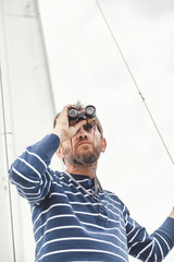 man with beard looking through binoculars sailing yacht