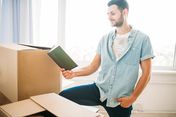 Man poses with book, moving to new home