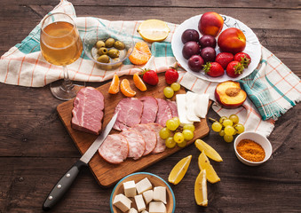 White wine and a set of meat delicacies, cheese and fruits on a dark, wooden background. Breakfast and cooking. View from above.
