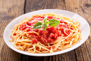 plate of pasta with tomato sauce and green basil