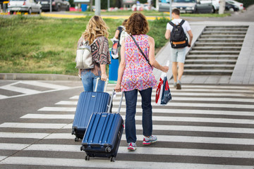 Woman in a colorful clothes with a blue suitcase crossing road