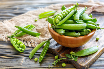 Wooden bowl with sweet pea pods.