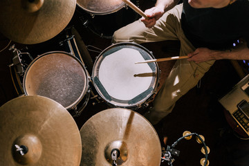 Drummer plays on drums top view. Live music concert, band rehearsal process