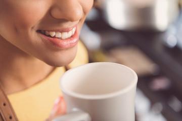Cheerful cute girl is enjoying beverage at work