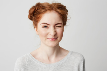 Close up of young cute redhead girl smiling looking at camera winking over white background.