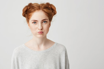 Portrait of young pretty ginger girl making funny face looking at camera over white background.