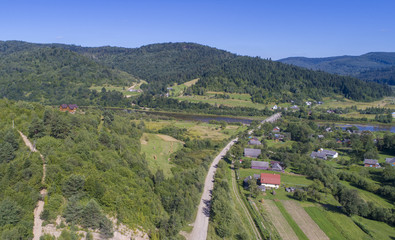 a beautiful summer landscape shot from a bird's eye view. mountains, river, green fields and villages.