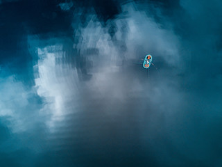 Aerial view of the lake with boat and reflecting clouds