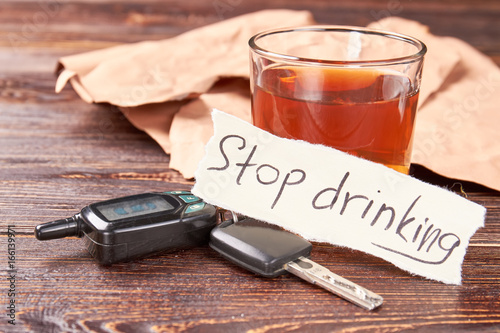 Automobile keys, message, glass of alcohol  Message stop