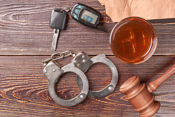 Gavel, key, handcuffs, whiskey, top view. Handcuffs, gavel, glass of whiskey, driving keys on wooden background.
