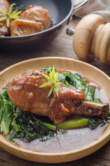 Baked chicken leg with vegetables and sauce on rustic wooden background