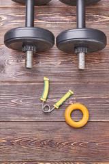Dumbbells, expanders on wooden floor. Vertical image of sport equipment lying on wooden background.
