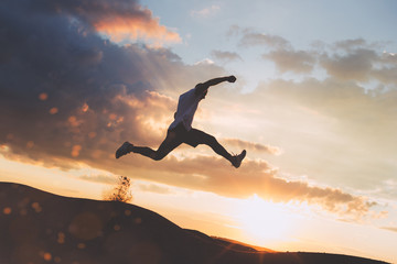Silhouette of extreme man running over the hills at beautiful sunset. Intentional dark colors