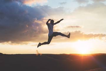 Silhouette of muscular man in a jumping pose against the background of a beautiful sky and sunset in nature. Intentional dark colors