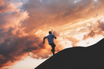 Male sportsman running around the hills at sunset. Athlete trains in nature
