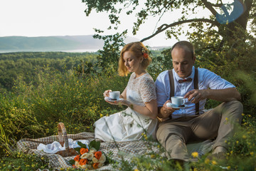 Attractive Couple Enjoying Romantic Sunset Picnic in the Countryside