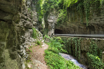 Deep Canyon with tunnels and a tiny road in northern Italy - Alps