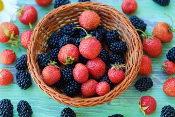 Blackberries and strawberries from the garden on wooden background