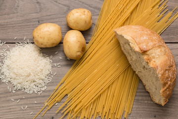 Spaghetti, rice, potatoes, and bread, on a wooden table