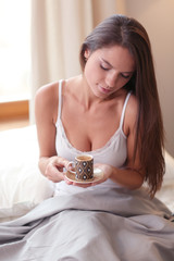 Young woman sitting in bed with a cup of milk