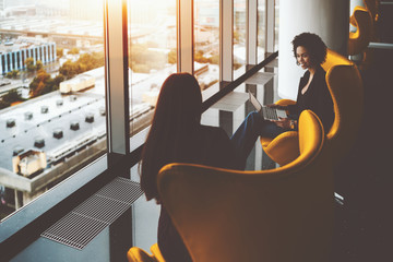 Smiling young black female probationer of business company is sitting with her colleague on yellow armchair in reflective luxury office interior near window, holding laptop and having conversation