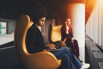 Young thoughtful afro american lady on yellow armchair is filling up table using laptop, her caucasian female colleague in defocused background having phone conversation, both are sitting near window