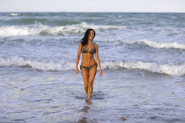 Woman walking out of the ocean