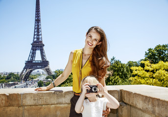 mother and daughter taking photo with camera in Paris, France
