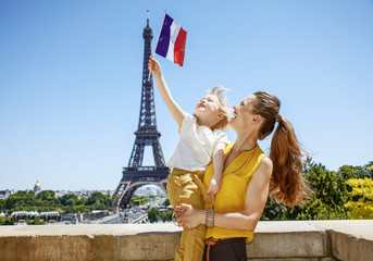 happy mother and child tourists rising flag in Paris, France