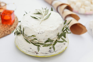 Cake for Wedding or Birthday party. White rustic cake with fresh olive branches