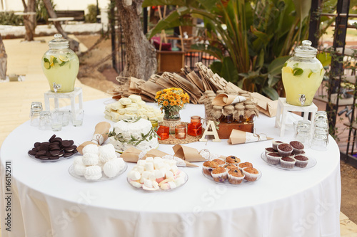 A festive round table setting with a lot of sweets muffins lemonade marsdhmallows & A festive round table setting with a lot of sweets: muffins ...