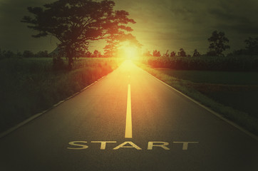 Conceptual image with text word start on asphalt road and sunset