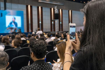 Speakers on the stage with Rear view of Audience taking photo or video for Live in the conference hall or seminar meeting, business and education about investment concept