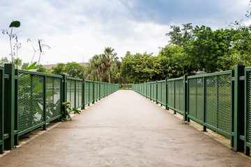 Concrete bicycle bridge with green fence in park