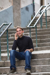 A young guy talking on mobile while sitting on the outdoor stairs.