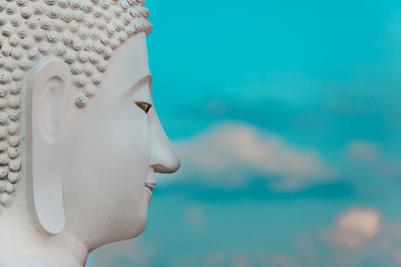 The side of the face of a white Buddha. The sky is bright as the background.