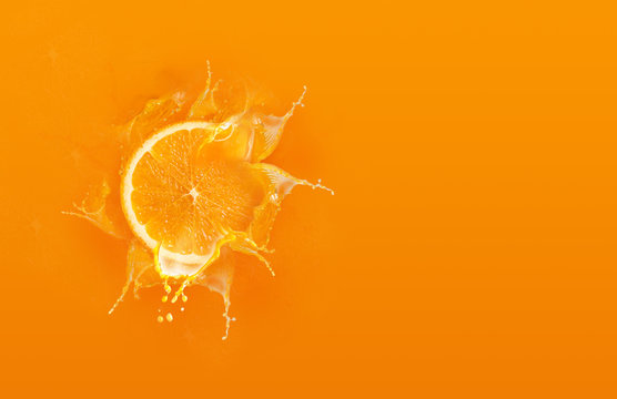 Slide cut piece of orange drop on orange background with orange juice splash water with copy space