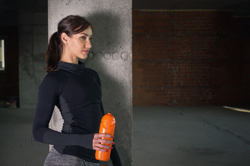 Young woman athlete in sportswear in gym in loft interior