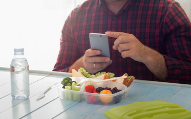 Man photographing lunch box with healthy food. Copy space