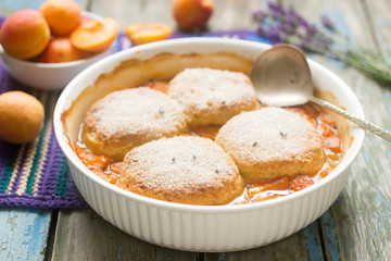 Homemade apricot cobbler with lavender on a wooden table. Selective focus.