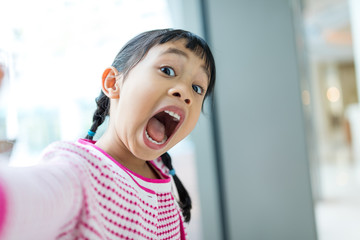 Asian little girl taking selfie with funny facial expression
